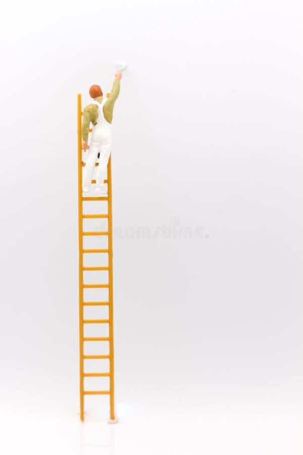 Miniaturowi ludzie, mini postać z drabiną i biel, malują przed ścianą obraz royalty free