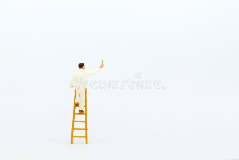 Miniaturowi ludzie: mini postać z drabinowym i białym obrazem przed ścianą zdjęcie stock