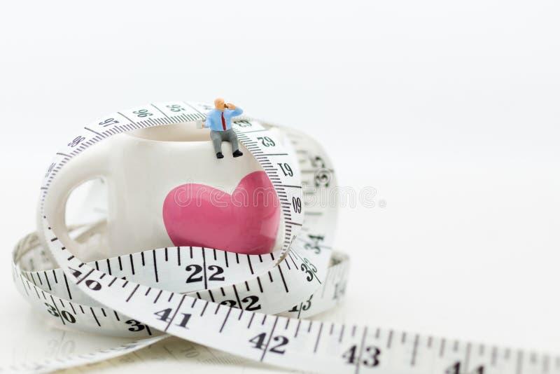 Miniaturowi ludzie: Obsługuje obsiadanie na szkle z talią wokoło i pijący kawę, ciastko Wizerunku use dla zdrowia pojęcia, bierze zdjęcie stock