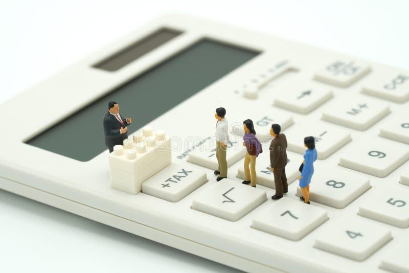 Miniaturowi ludzie Płacą kolejka rocznego dochodu podatek dla roku na kalkulatorze używać jako tła biznesowy pojęcie i finanse co fotografia royalty free