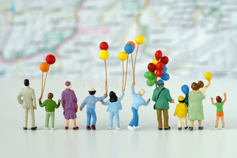 Miniaturowi ludzie patrzeje mapę w t z rodzinnym mienie balonem obraz stock