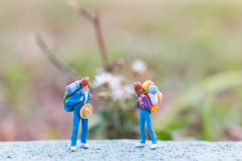 Miniaturowi ludzie: Podróżnik z plecak podróżą i trekking C obrazy royalty free