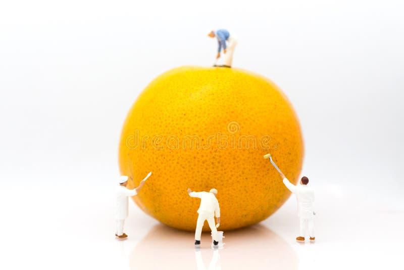 Miniaturowi ludzie: Pracownicy malują kolor na pomarańczowych łupach Wizerunku use dla twórczości, biznesowy pojęcie fotografia royalty free
