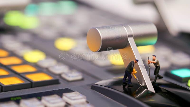 Miniaturowi ludzie: pracownik na switcher kontrola Telewizyjny Broa zdjęcie royalty free