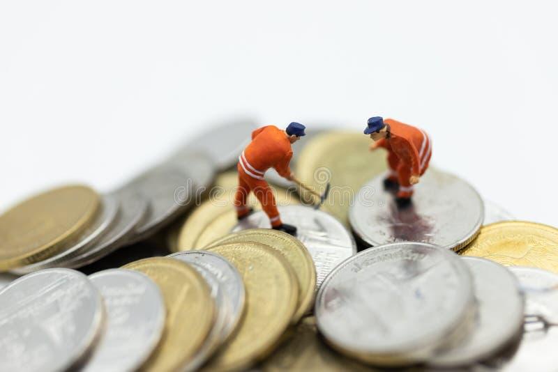 Miniaturowi ludzie: Pracownik pracuje na stercie monety, dochód od pracy Wizerunku use dla biznesowego pojęcia obraz royalty free