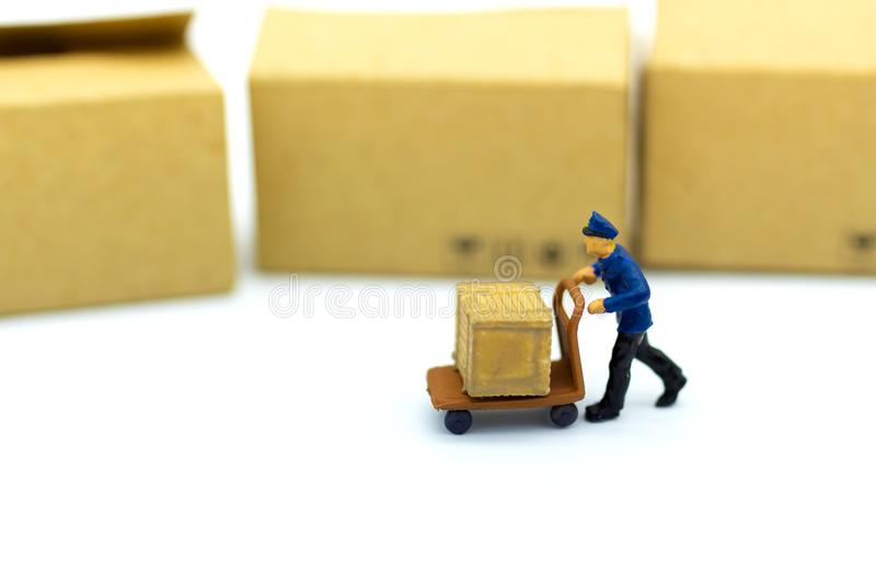Miniaturowi ludzie: Pracownik z udźwigów narzędziami z pudełkiem w magazynie Wizerunku use dla przemysłowego i logistycznie pojęc obraz royalty free