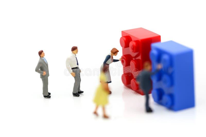 Miniaturowi ludzie: pracownika pchnięcia guzika dzieciaka kolorowe zabawki zdjęcia stock