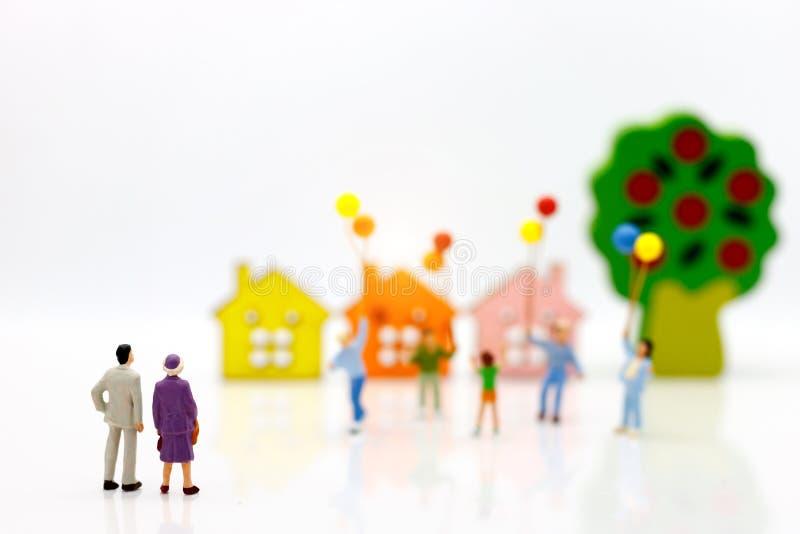 Miniaturowi ludzie: rodzice patrzeje dziecko sztukę i trzyma bal zdjęcie stock