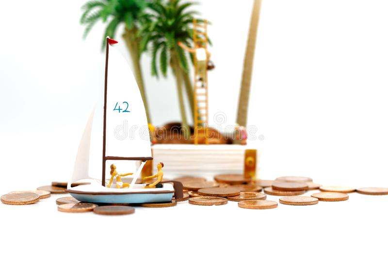 Miniaturowi ludzie siedzi na żaglówce która żłobi na monetach Mon zdjęcie stock