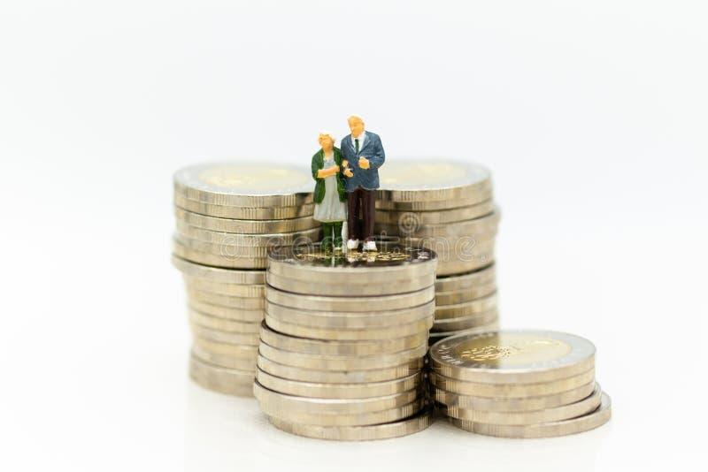 Miniaturowi ludzie, stara pary postaci pozycja na górze stert monet Wizerunku use dla tło emerytura planowania, ubezpieczenie na  zdjęcie stock