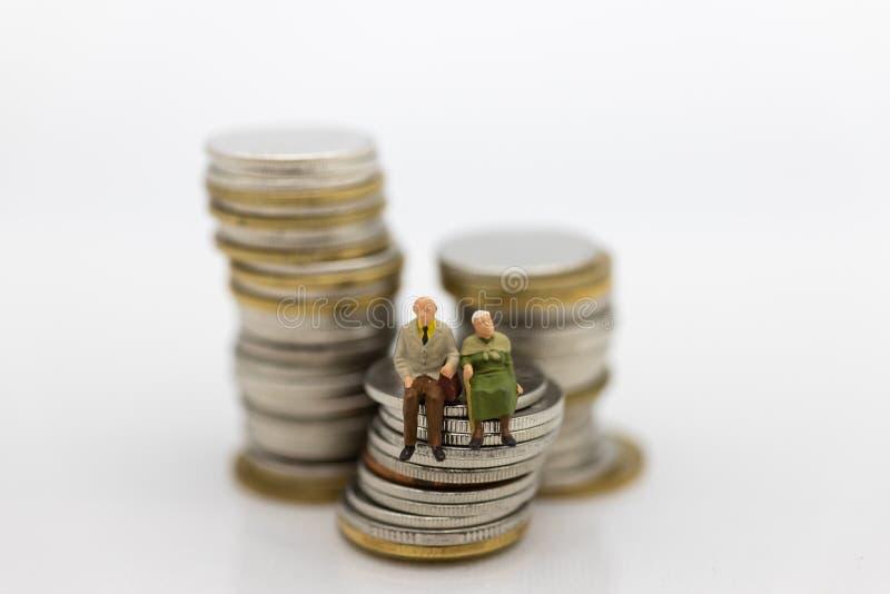 Miniaturowi ludzie, Stary pary postaci obsiadanie na górze sterty ukuwają nazwę używać jako tło emerytura planowanie, ubezpieczen zdjęcie stock