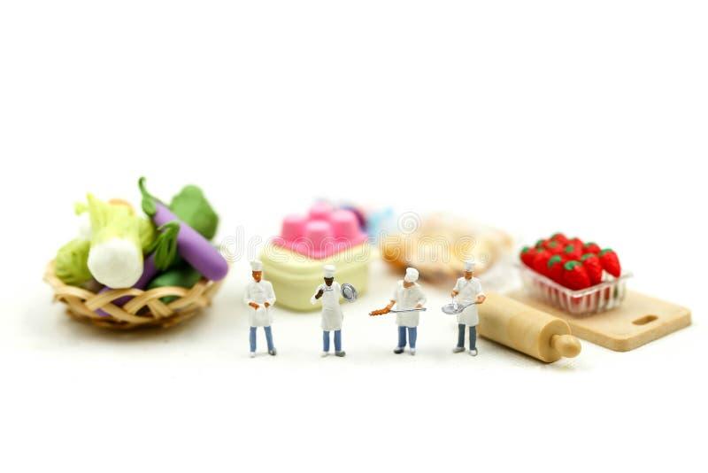 Miniaturowi ludzie: Szef kuchni z asortymentem świezi owoc i warzywo, kulinarny pojęcie fotografia stock