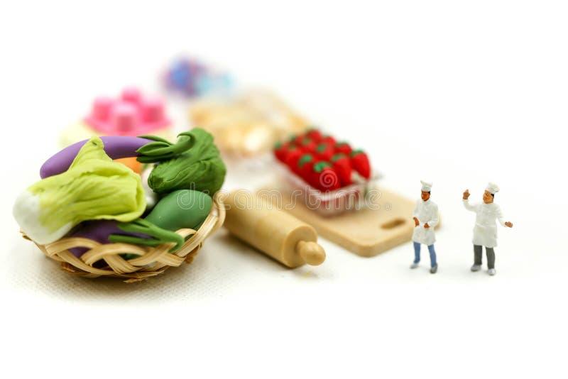 Miniaturowi ludzie: Szef kuchni z asortymentem ?wiezi owoc i warzywo, kulinarny poj?cie obraz royalty free