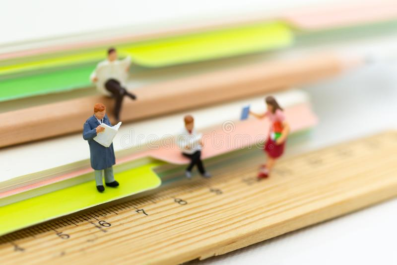 Miniaturowi ludzie: Ucznie czytający książka Wizerunku use dla uczyć się, edukaci pojęcie fotografia stock