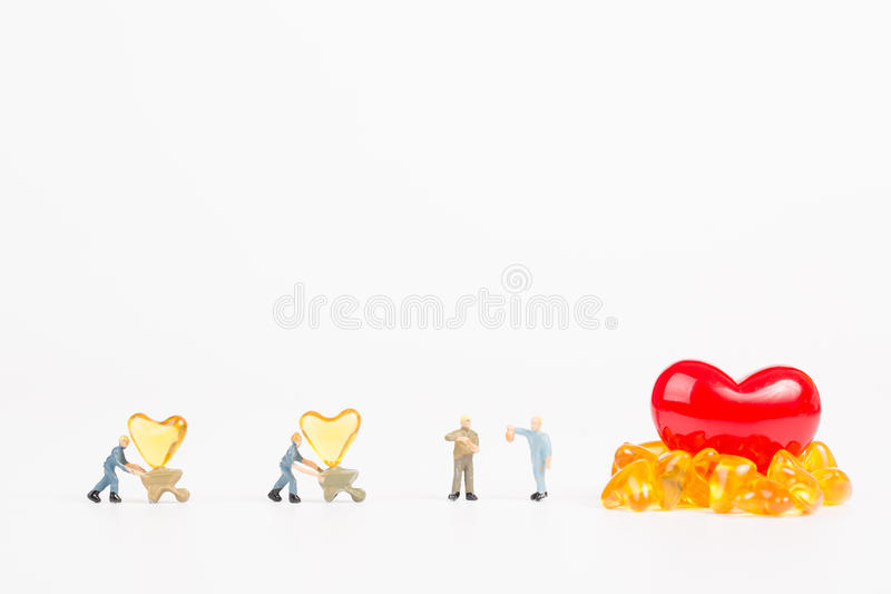 Miniaturowi ludzie z dorsz wątróbki olejem zdjęcia stock