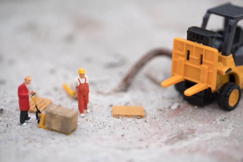 Miniaturowi magazynowi pracownika forklift przewożenia towary boksują semi przewozić samochodem z przyczepą obrazy stock
