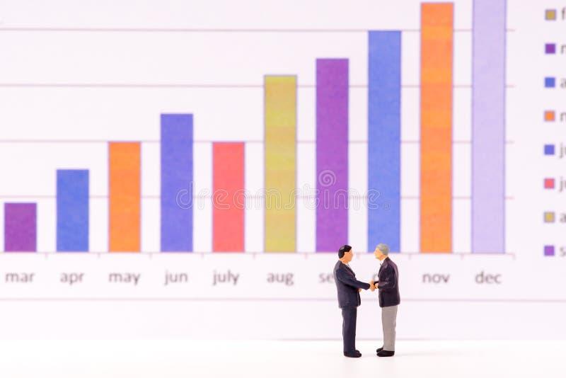 Miniaturowi postaci ludzie biznesu patrzeje prętowego wykres sporządzają mapę zdjęcia stock