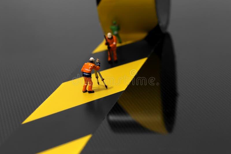 Miniaturowi szalkowego modela pracownicy budowlani używa zagrożenie taśmy zdjęcie stock