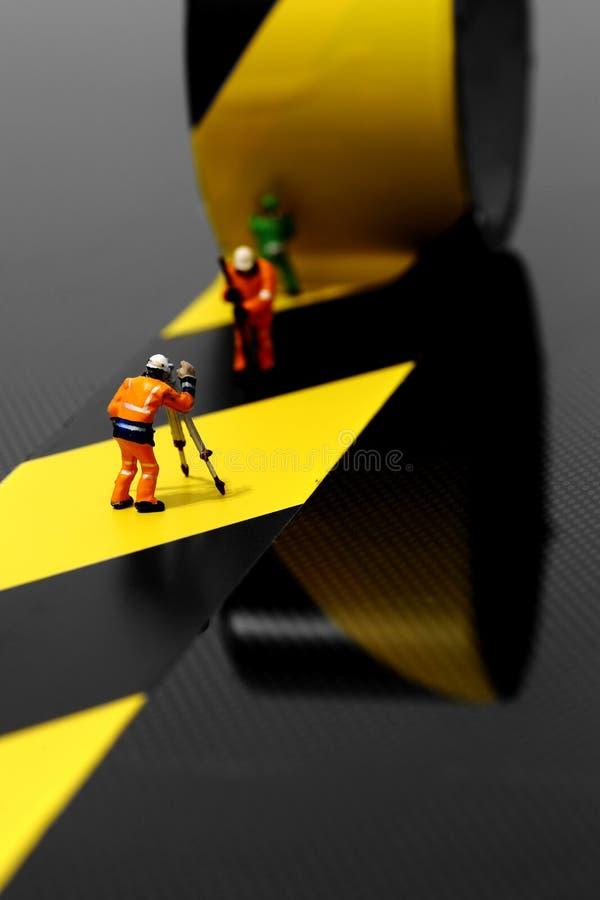 Miniaturowi szalkowego modela pracownicy budowlani używa zagrożenie taśmy zdjęcia stock