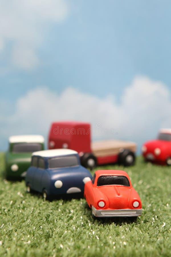 Miniaturowi zabawkarscy samochody na zielonej trawie nad niebieskim niebem i chmurami obrazy stock