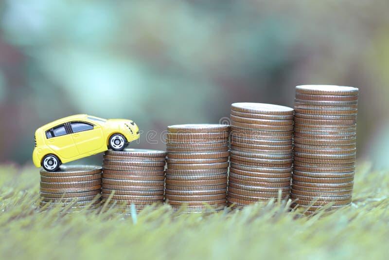 Miniaturowy żółty samochodu model na dorośnięcie stercie moneta pieniądze na natury zieleni tle, oszczędzanie pieniądze dla samoc obrazy royalty free
