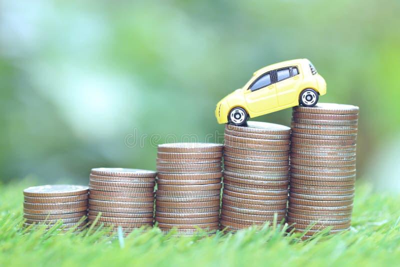 Miniaturowy żółty samochodu model na dorośnięcie stercie moneta pieniądze na natury zieleni tle, oszczędzanie pieniądze dla samoc zdjęcia stock