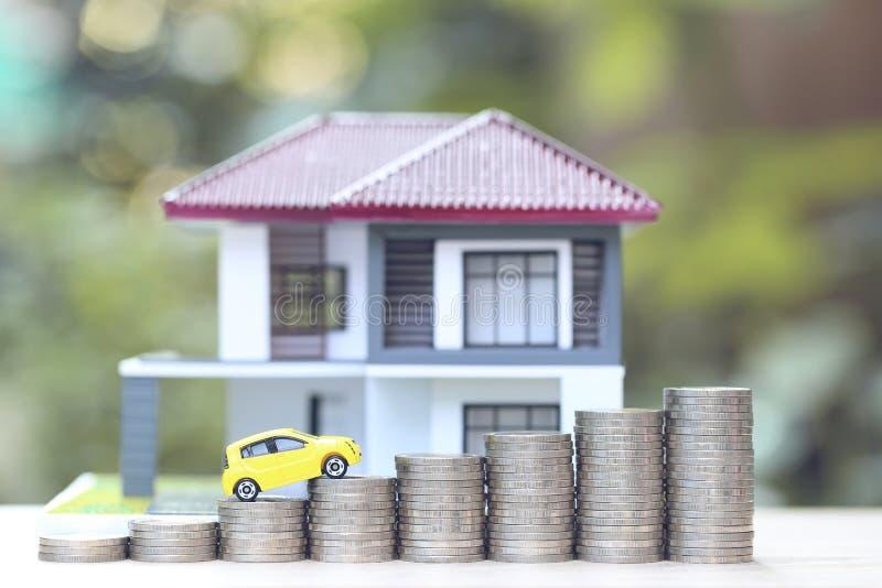 Miniaturowy żółty samochodu model na dorośnięcie stercie monety pieniądze i modela dom na naturze zieleniejemy tło, oszczędzanie  zdjęcie royalty free