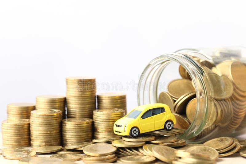 Miniaturowy żółty samochodu model na stercie moneta pieniądze w szklanej butelce na wtite tle, Ratuje pieniądze dla samochodu, fi obrazy stock