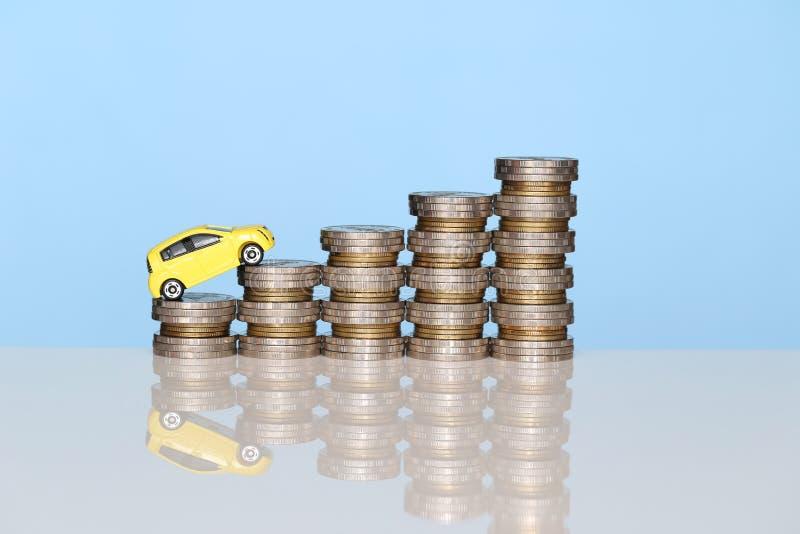 Miniaturowy żółty samochodu model na dorośnięcie stercie moneta pieniądze na błękitnym tle, oszczędzanie pieniądze dla samochodu, zdjęcie stock