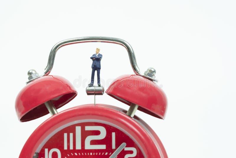 Miniaturowy biznesmen z czerwonym budzikiem zdjęcia stock