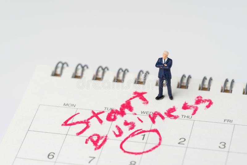 Miniaturowy biznesmen z zaufanie pozycją na bielu kalendarzu z okręgiem na dacie i tekst Zaczynamy biznes używać jako decyzja obrazy stock