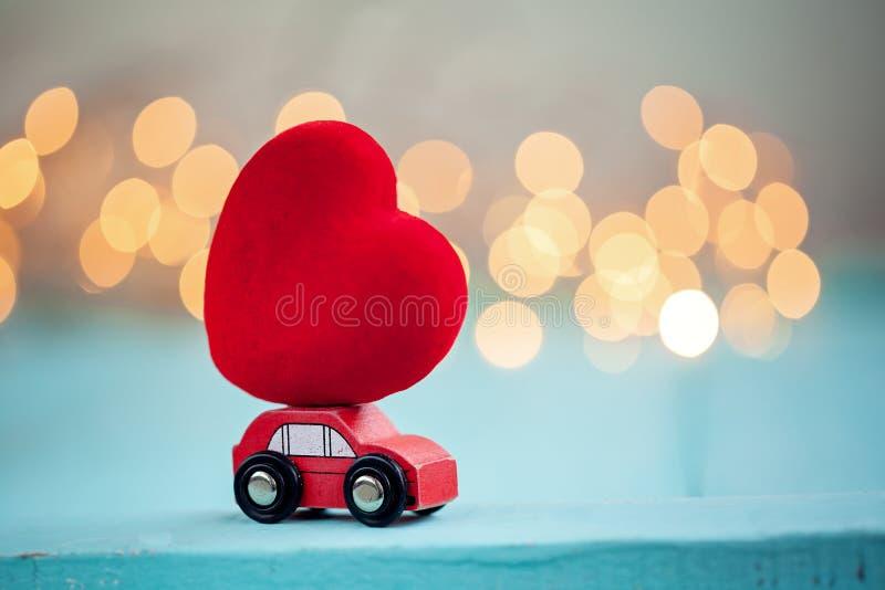 Miniaturowy czerwony samochód niesie czerwonego dużego serce na połysku bokeh tle obraz royalty free