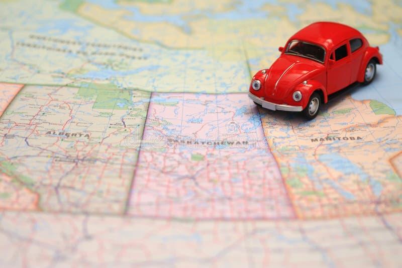 Miniaturowy czerwony samochodowy jeżdżenie na mapie pairie prowincje, Canada zdjęcie stock