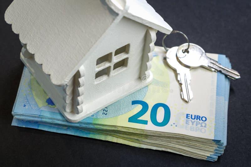 Miniaturowy dom, plik pieniądze i klucze, jesteśmy na czarnej powierzchni fotografia royalty free