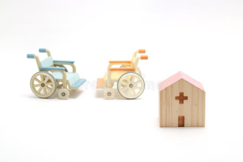 Miniaturowy drewniany szpital i wózki inwalidzcy na białym tle zdjęcie royalty free