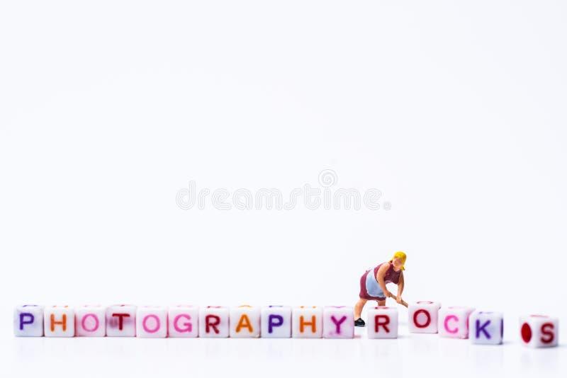 Miniaturowy figurki kobiety naprawianie przystosowywa grupy listy tworzy słów Literować zdjęcie stock