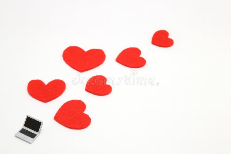 Miniaturowy laptop i niektóre czerwoni serca na białym tle fotografia royalty free
