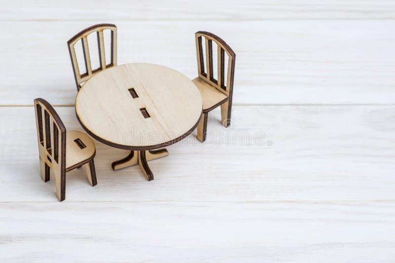 Miniaturowy nieociosany drewniany meble na drewnianym tle Roczników krzesła z kopii przestrzenią i stół zdjęcia stock