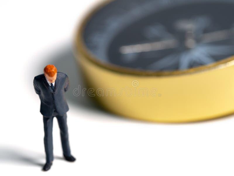 Miniaturowy postać biznesmen w zmroku - błękitna kostium pozycja na stronie złoty kompas Pojęcie dla znajdować sposób dlaczego su zdjęcie royalty free