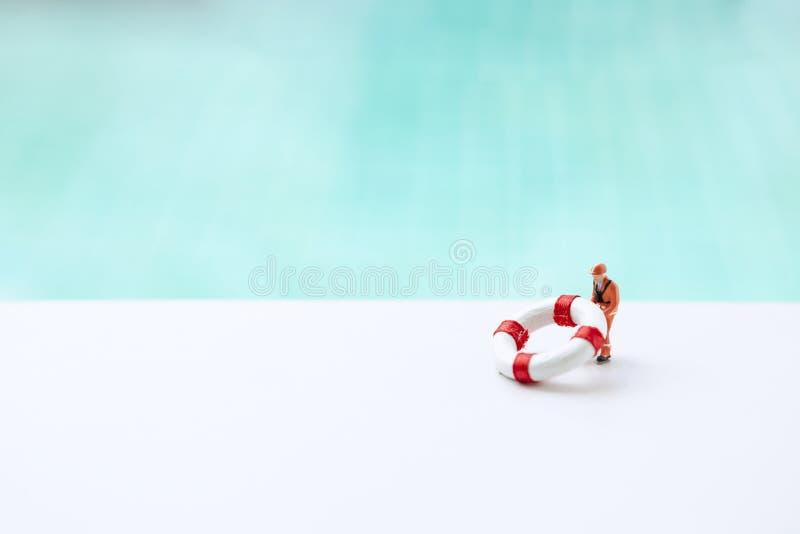 Miniaturowy pracownik z mały życia boja nad zamazanym błękitnym pływackiego basenu wody tłem, życie strażnik zdjęcia royalty free