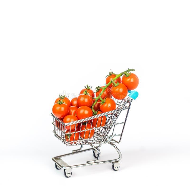 Miniaturowy wózek na zakupy wypełniał z malutkimi czereśniowymi pomidorami odizolowywającymi fotografia stock