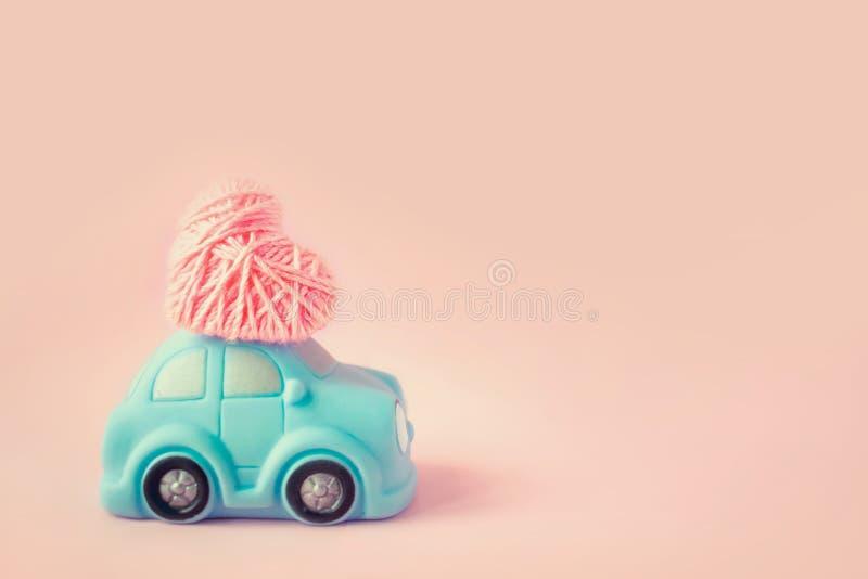 Miniaturowy zabawkarski błękitny samochodowy dostarcza różowy niciany serce dla Valentin fotografia stock