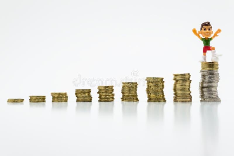 Miniaturowy zabawkarski mężczyzna z futbolową pozycją na dorośnięcie monetach Pojęcie rywalizacja i zwycięstwo zdjęcie stock