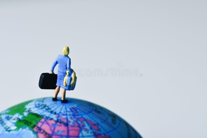 Miniaturreisendfrau auf der Kugel lizenzfreie stockbilder