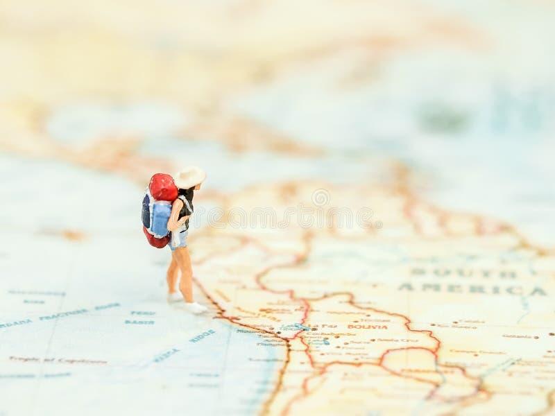 Miniaturreisendfrauen mit dem Rucksack, der auf Wold steht, zeichnen für Reise auf der ganzen Welt auf lizenzfreies stockfoto