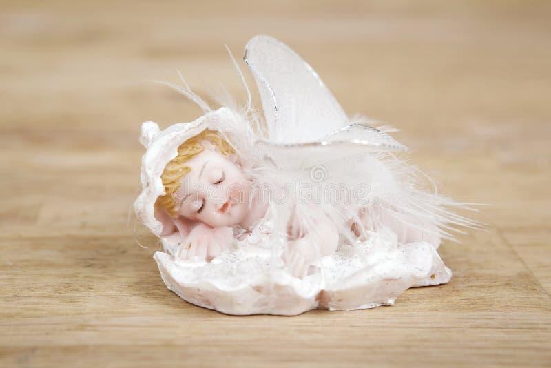 Miniaturstatue des weißen Engels mit Flügeln auf Holzoberfläche lizenzfreies stockfoto