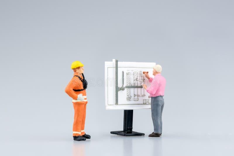 Miniaturtechnikleute und -architektur, die an Bauzeichnung arbeitet lizenzfreie stockfotos