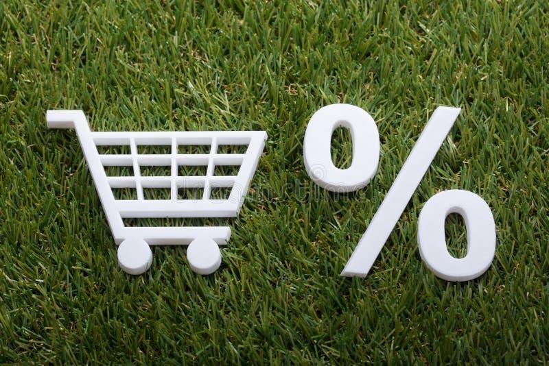 Miniaturwarenkorb-und Prozentsatz-Zeichen auf grünem Gras lizenzfreie stockbilder