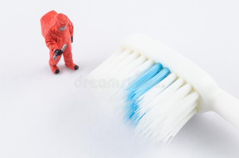 Miniaturwissenschaftler, der Bakterien auf der Zahnbürste überprüft stockbild