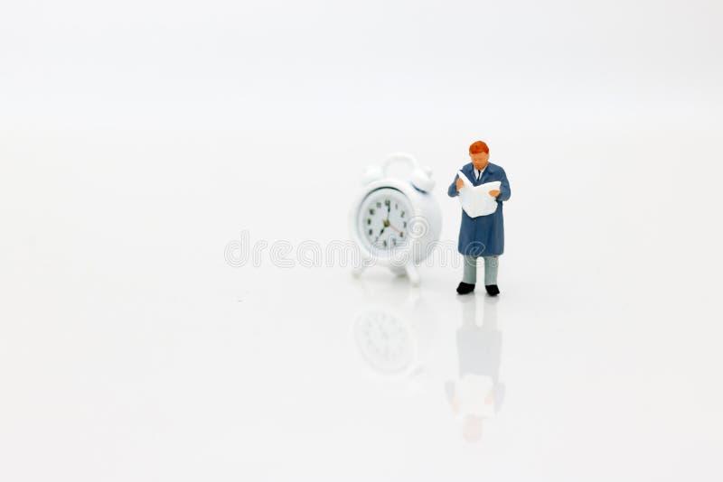 Miniatury zaludniają czytelniczą książkę z zegarem, pojęcie educa zdjęcia royalty free